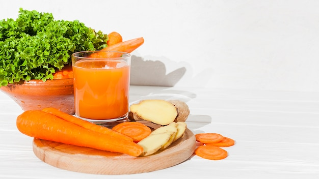 Verduras y vegetación con zumo en mesa. Foto gratis