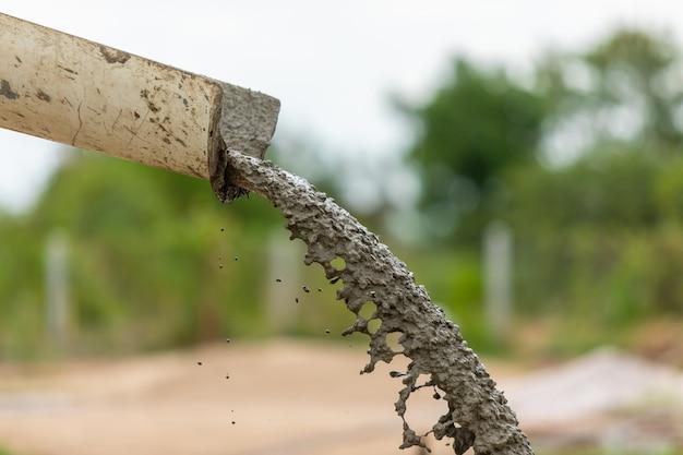 Verter y barrer el cemento húmedo en el piso en proceso de construcción de viviendas Foto Premium