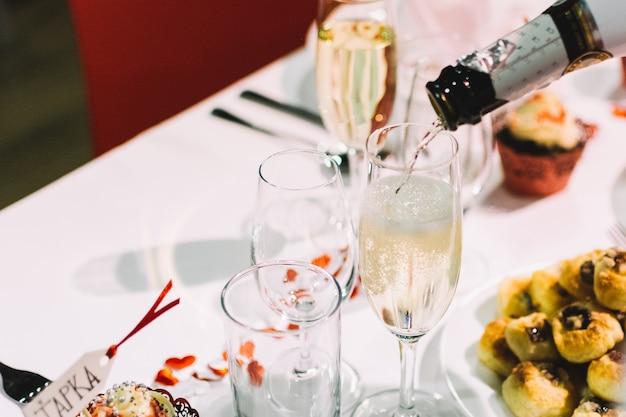 Verter un brindis de champán en una fiesta de celebración de la boda Foto gratis