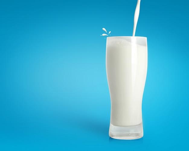 Verter la leche fresca en vidrio sobre fondo azul Foto Premium