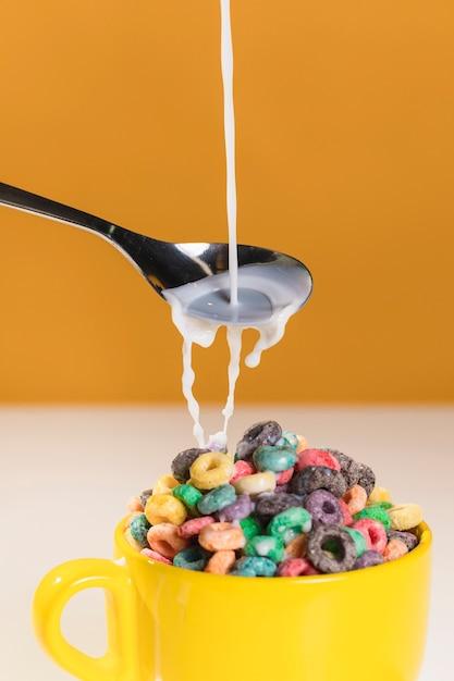 Verter la leche sobre un tazón con cereales Foto gratis