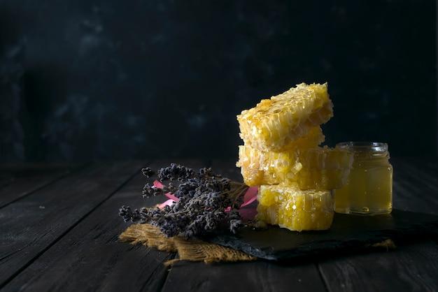 Verter miel en panal de miel con flores de lavanda sobre fondo oscuro piedra Foto Premium