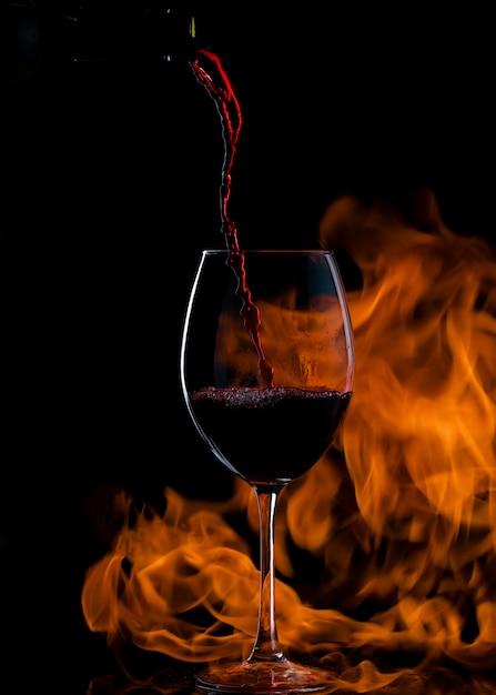 Verter vino tinto en vaso con tallo largo, con fuego en el fondo Foto gratis