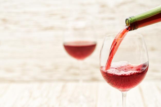 Verter vino tinto en los vasos contra la mesa de madera blanca Foto Premium