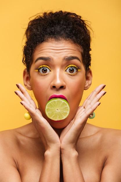 Vertical sorprendió a la mujer afroamericana ojos saltones al poner la mitad de la cal fresca en la boca aislada, sobre la pared amarilla Foto gratis
