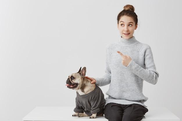 Vestido de bulldog francés con alegre dueña. mujer en suéter gris sentado en el escritorio señalando con el dedo índice prestando atención a algo curioso. emociones humanas positivas, expresión facial Foto gratis