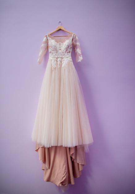 Vestido de novia en color de rosa polvorienta cuelga en la pared ...