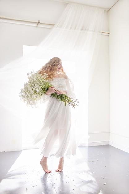 Vestido de niña de luz blanca y pelo rizado con flores. Foto Premium