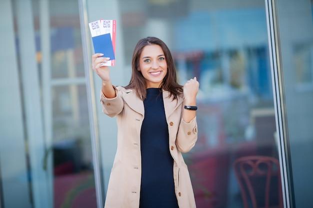 Viajar. mujer joven alegre que sostiene boletos de avión al aire libre Foto Premium