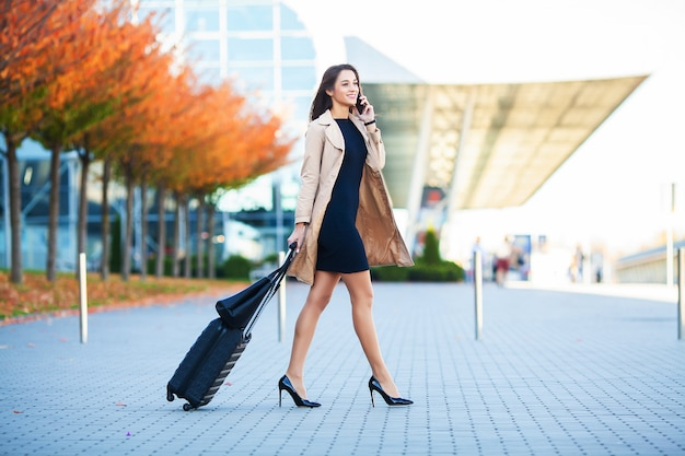 Viajar. mujer de negocios en el aeropuerto hablando por el teléfono inteligente mientras camina con equipaje de mano en el aeropuerto va a la puerta. Foto Premium