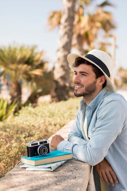 Viajero apoyado contra una valla Foto gratis