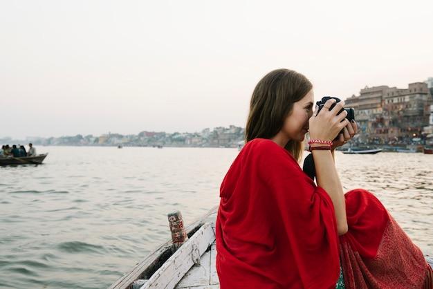 Viajero en un barco tomando fotos desde el río ganges Foto gratis