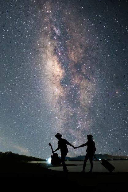 Viajero de pareja de pie cerca del lago y mirando la vía láctea y ...