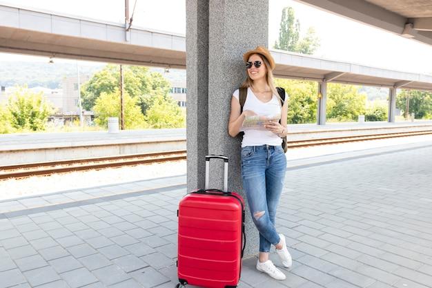Viajero en la estación de tren con su equipaje Foto gratis