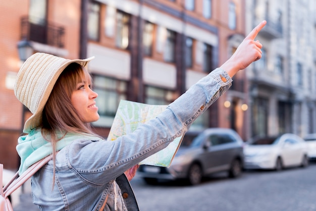 Viajero femenino feliz que sostiene el mapa en la mano que señala en algo en la ciudad Foto gratis