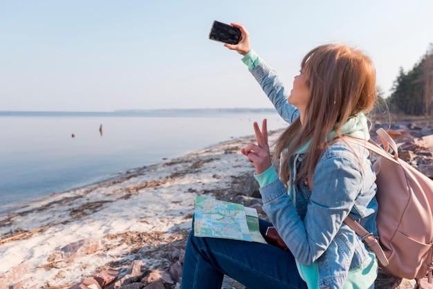 Viajero femenino que se sienta en la playa que toma el selfie en el teléfono móvil Foto gratis