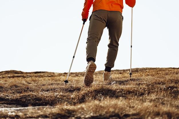 Viajero hombre con bastones de trekking subiendo la montaña Foto Premium