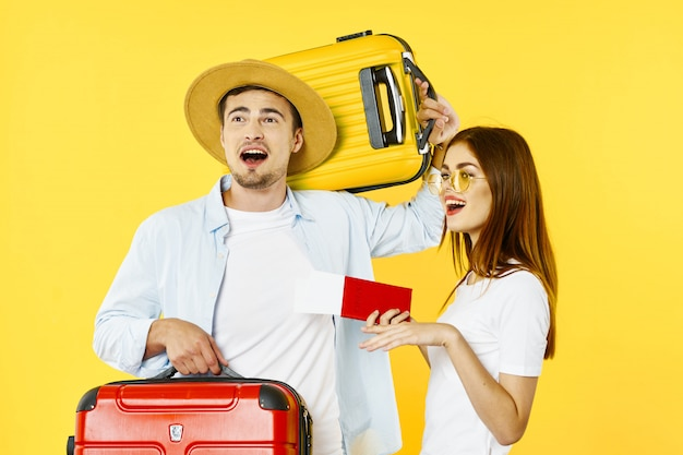 Viajero de hombre y mujer con una maleta, fondo de color, alegría, pasaporte Foto Premium