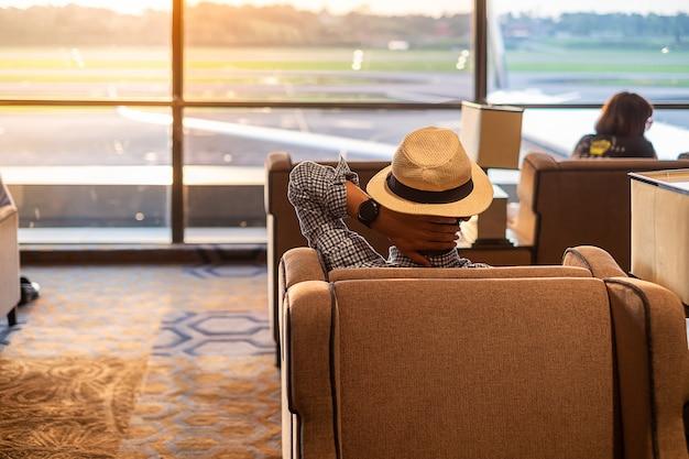 Viajero del hombre con el sombrero que mira al aeroplano en la salida del sol de la mañana Foto Premium