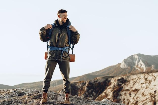 Viajero joven caucásico con mochila grande senderismo en las montañas Foto Premium