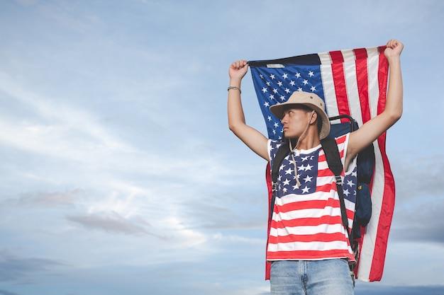 Viajero levanta una bandera frente a la vista del cielo Foto gratis