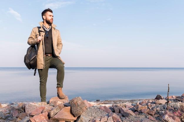 Viajero masculino hermoso que se coloca delante del mar que sostiene el bolso en el hombro que mira lejos Foto gratis