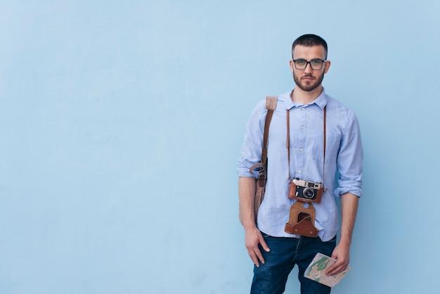 Viajero masculino joven con la cámara alrededor de su cuello que se coloca cerca de fondo azul Foto gratis