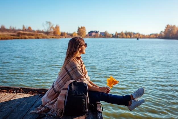 Viajero con mochila relajante por otoño río al atardecer. mujer joven sentada en el muelle admirando el paisaje Foto Premium