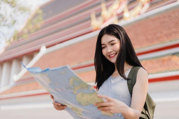 Viajero mujer asiática dirección en mapa de ubicación en bangkok, tailandia Foto gratis