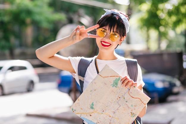 Viajero mujer feliz con sonrisa encantadora posando con el signo de la paz de pie delante de coches coloridos Foto gratis