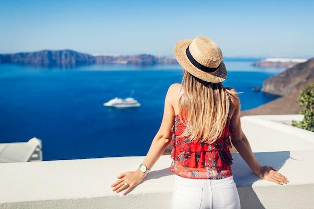 Viajero mujer mirando caldera de fira o thera, isla de santorini, grecia. turismo, viajes, concepto de vacaciones Foto Premium