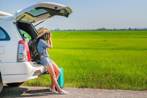 Viajero de mujer sentado en el portón de un auto y tomando una foto Foto Premium