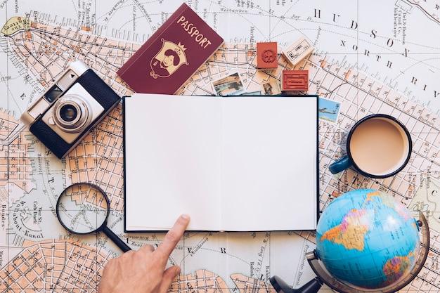 Viajero que señala en el bloc de notas en blanco Foto gratis
