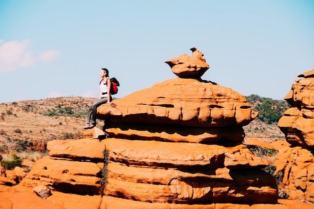 Un viajero sentado en una roca en la meseta sudafricana de magaliesberg Foto Premium