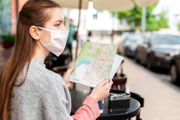 Viajero sentado y usando un mapa Foto gratis