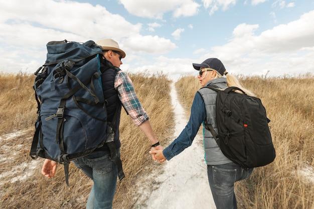 Viajeros adultos tomados de la mano al aire libre Foto gratis