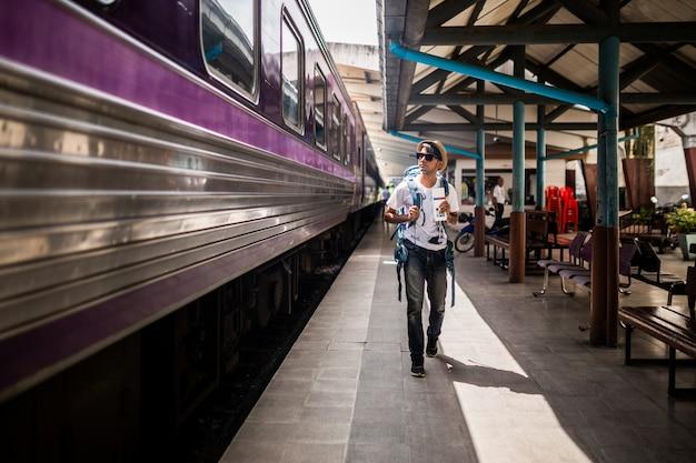 Viajeros mochileando y caminando solo en la estación de tren. Foto Premium