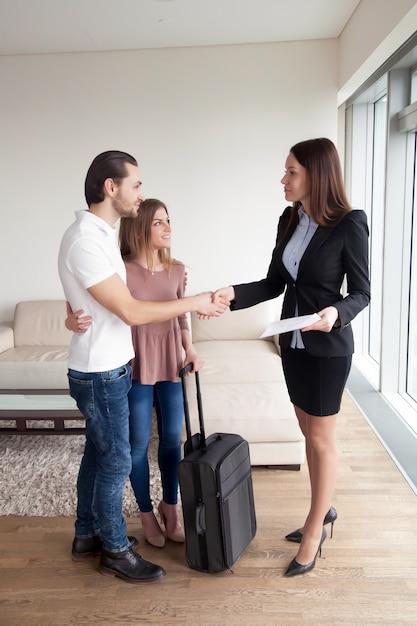 Viajeros que alquilan propiedades, pareja dándose la mano con agente inmobiliario. Foto gratis