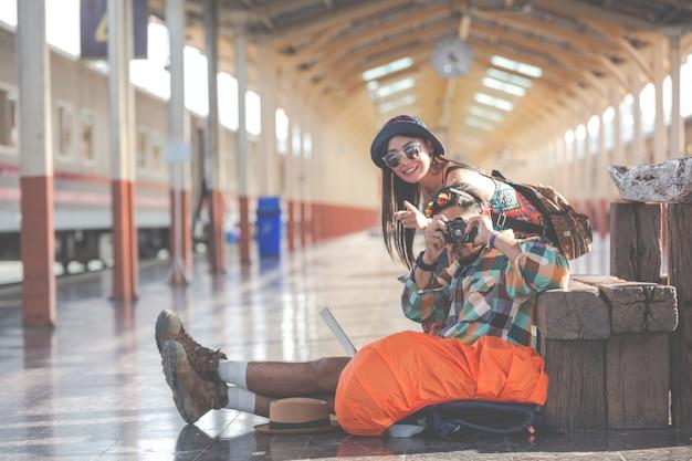 Los viajeros toman fotos de parejas mientras esperan los trenes. Foto gratis