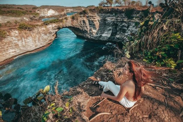 Viajes mujer mirando vista de playa rota, isla de nusa penida bali, indonesia Foto Premium
