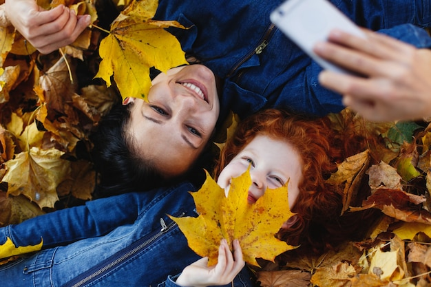 Vibraciones otoñales, retrato de familia. la encantadora mamá y su hija pelirroja se divierten tomando un selfie en sm Foto gratis