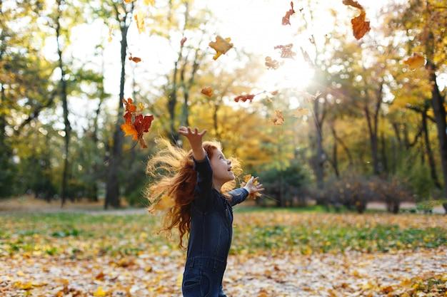 Vibraciones otoñales, retrato infantil. encantadora y roja niña de pelo se ve feliz caminando y jugando en t Foto gratis