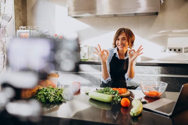 Videoblogger joven cocinando en la cocina y filmando Foto gratis
