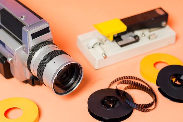 Videocámara con tira de película sobre fondo color melocotón con tira de película sobre fondo color melocotón Foto gratis