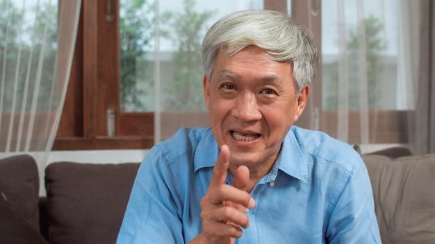 Videollamada asiática del hombre mayor en casa. varón chino mayor mayor asiático que usa la videollamada del teléfono móvil que habla con los niños del nieto de la familia mientras que miente en el sofá en concepto de la sala de estar en casa. Foto gratis
