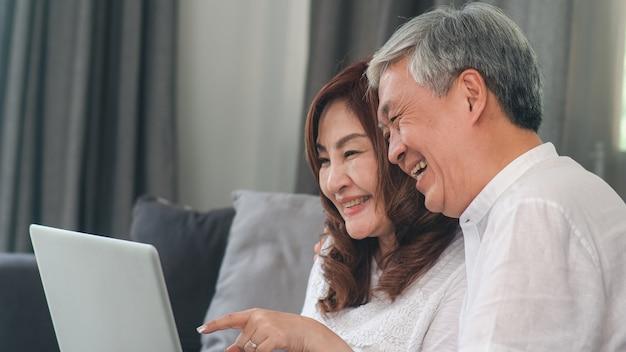 Videollamada asiática mayor de los pares en casa. abuelos chinos mayores asiáticos, usando la videollamada del ordenador portátil que habla con los niños del nieto de la familia mientras que miente en el sofá en concepto de la sala de estar en casa. Foto gratis