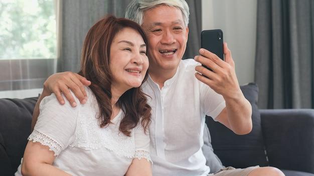 Videollamada asiática mayor de los pares en casa. abuelos chinos mayores asiáticos, usando la videollamada del teléfono móvil que habla con los niños del nieto de la familia mientras que miente en el sofá en concepto de la sala de estar en casa. Foto gratis