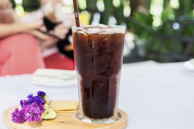 Vidrio americano frío en la mesa de cubierta de tela blanca - concepto de bebida fría y relajada Foto gratis
