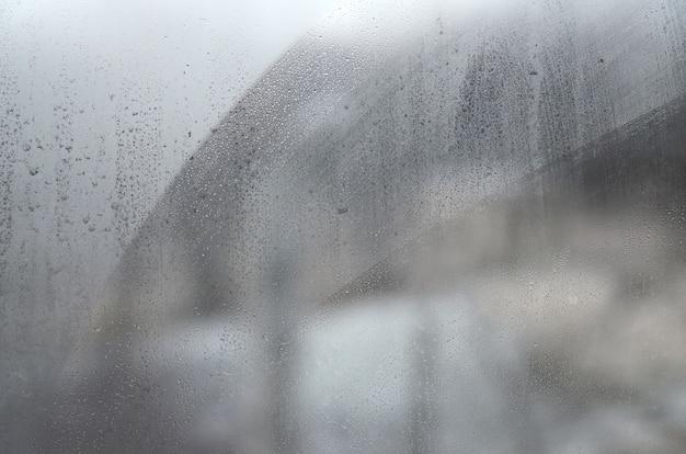 Vidrio de ventana con condensado o vapor después de lluvia intensa, textura o imagen de fondo Foto Premium