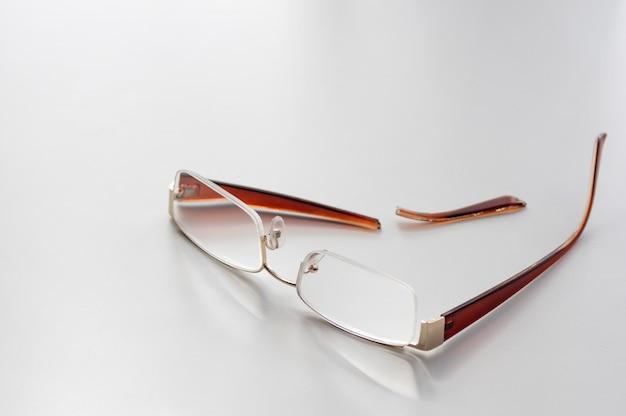 Vidrios quebrados en un fondo blanco. aro roto de las gafas. Foto Premium